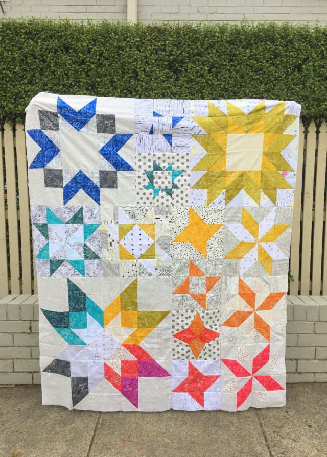 An Alison Glass rainbow quilt using the Aurora pattern from BlossomHeartQuilts.com