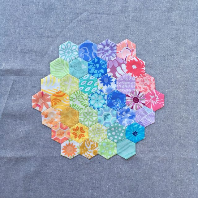 An English paper pieced Kate Spain rainbow hexagon on Essex Linen by BlossomHeartQuilts.com