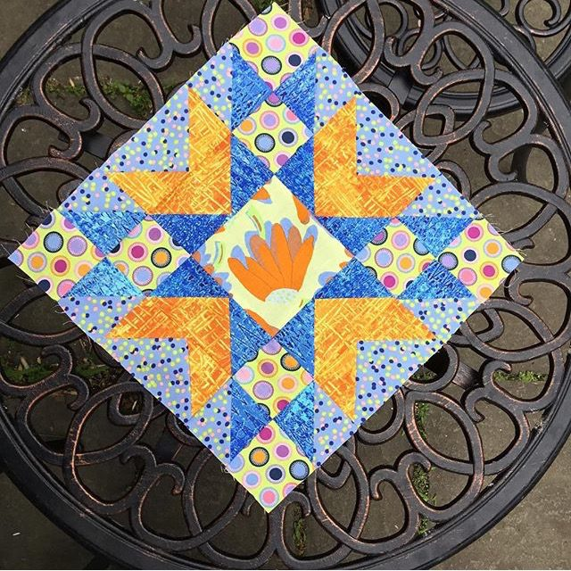 An orange and blue Double Star quilt block from the free pattern at BlossomHeartQuilts.com