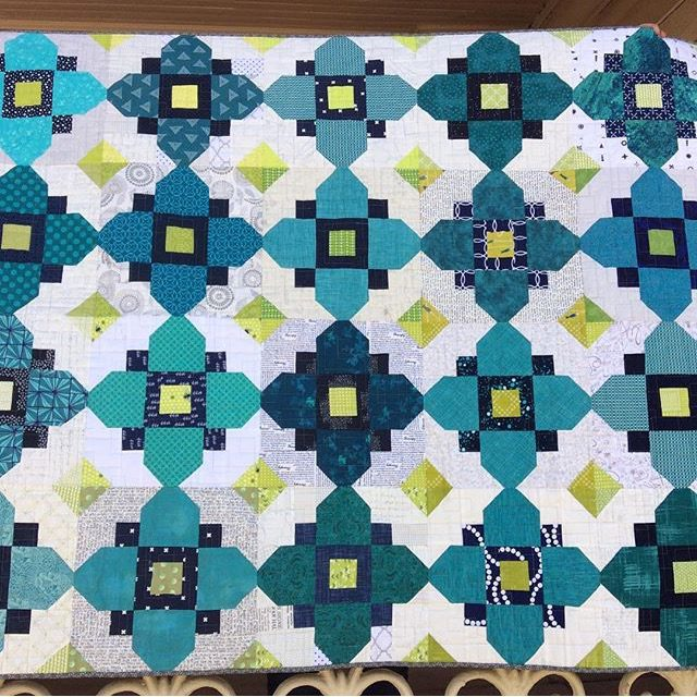 A teal Quatrefoil quilt made from the free quilt block pattern at BlossomHeartQuilts.com