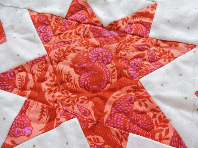 Free motion quilting outlining Tula Pink fabric on Geode quilt by BlossomHeartQuilts.com