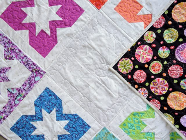 Mary Engelbreit fabric matching Tula Pink rainbow quilt using Geode quilt pattern by BlossomHeartQuilts.com