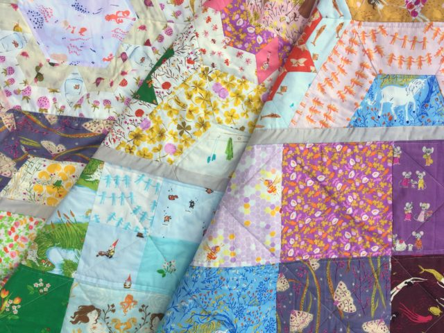 A quilt mixing EPP with patchwork using Heather Ross fabric by BlossomHeartQuilts.com