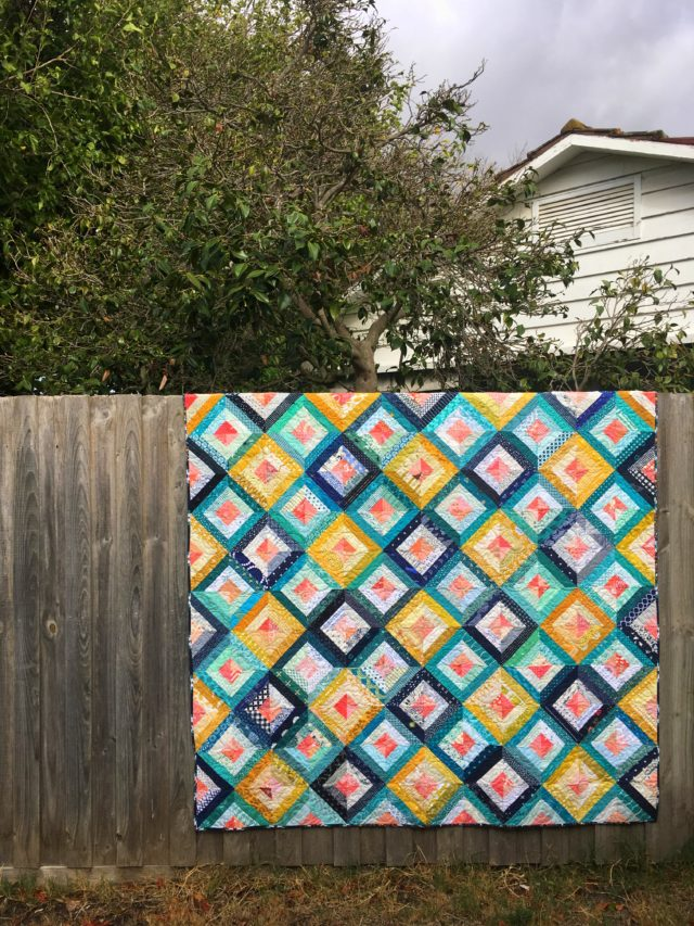 Scrap quilt using Treasure Hunt quilt block tutorial in navy, mustard, teal and coral by BlossomHeartQuilts.com